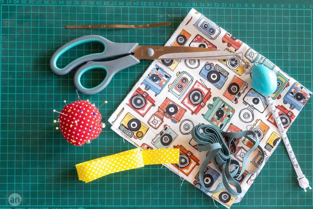Für eine Maske benötigt man: Stoff 20 x 40 cm, Gummiband 2mal 16 cm, 2mal 9 cm Schrägband, einen Draht 15 cm oder den Metallstreifen aus einem Heftstreifen, Schere, Stecknadeln, Maßband, Faden und eine Nähmaschine.